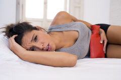 Young beautiful hispanic woman holding hot water bottle against belly suffering menstrual period pain Stock Image