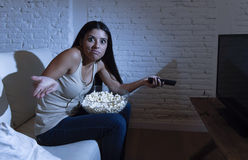 Young beautiful hispanic woman at home watching television angry and upset about tv programs Royalty Free Stock Images