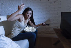 Young beautiful hispanic woman at home watching television angry and upset about tv programs stock images