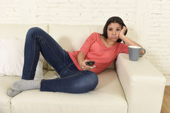 Young beautiful hispanic woman at home watching television tired and bored stock photography