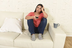 Young beautiful hispanic woman at home watching television tired and bored stock photo