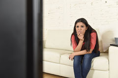 Young beautiful hispanic woman at home watching television tired and bored stock images
