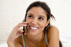Young beautiful hispanic woman talking relaxed on mobile phone in bed Royalty Free Stock Photo