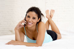 Young beautiful hispanic woman talking relaxed on mobile phone in bed Royalty Free Stock Image