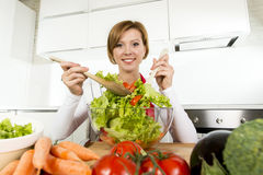 Young beautiful home cook woman at modern kitchen preparing vegetable salad bowl smiling happy Royalty Free Stock Images