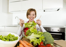 Young beautiful home cook woman at modern kitchen preparing vegetable salad bowl smiling happy Royalty Free Stock Photo