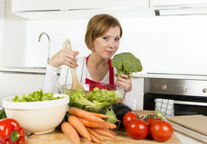 Young beautiful home cook woman at modern kitchen preparing vegetable salad bowl smiling happy Stock Images