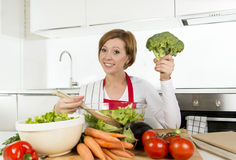 Young beautiful home cook woman at modern kitchen preparing vegetable salad bowl smiling happy Stock Photo