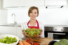 Young beautiful home cook woman at modern kitchen preparing vegetable salad bowl smiling happy. Young beautiful home cook woman at modern domestic kitchen Royalty Free Stock Images