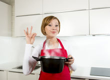 Young beautiful home cook woman in red apron at domestic kitchen Royalty Free Stock Images