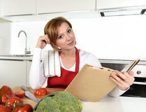 Young beautiful home cook woman in red apron at modern domestic kitchen reading cookbook following recipe Royalty Free Stock Images