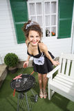 Young beautiful housemaid fry sausage on brazier. Near white house Stock Photos