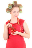 Young beautiful housewife with hair curlers and tomato Stock Image