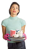 Young beautiful housewife with pile of dishes. Portrait of a young beautiful housewife holding a pile of dirty dishes and looking fed up. Isolated over white Stock Image