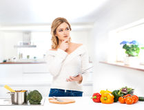 Young and beautiful housewife woman cooking in the kitchen Royalty Free Stock Image
