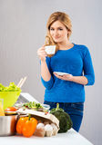 Young and beautiful housewife woman cooking in a kitchen Royalty Free Stock Photography