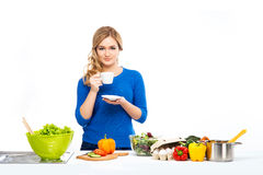 Young and beautiful housewife woman cooking in a kitchen Stock Images