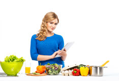 Young and beautiful housewife woman cooking in a kitchen Royalty Free Stock Image