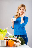 Young and beautiful housewife woman cooking in a kitchen Stock Photos