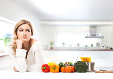 Young and beautiful housewife woman in a kitchen Royalty Free Stock Image