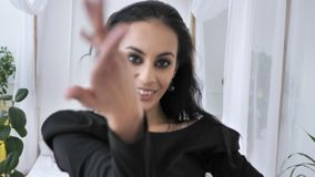 Young beautiful indian brunette girl dancing belly dancing, Indian national dance, in a black dress in a white room in. The background 50 fps 4k stock video