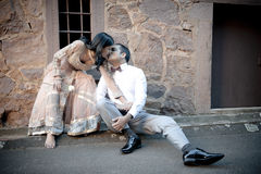 Young beautiful Indian couple kissing against stone wall outdoors. With single white rose Royalty Free Stock Photos