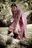 Young beautiful Indian Hindu bride standing under tree. Adjusting shoe strap Royalty Free Stock Photography