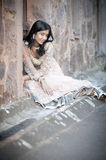 Young beautiful Indian Woman sitting against stone wall outdoors Stock Photo
