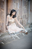 Young beautiful Indian Woman sitting against stone wall outdoors Royalty Free Stock Images