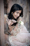 Young beautiful Indian Woman sitting against stone wall outdoors Stock Photos