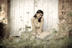 Young beautiful Indian Woman sitting against white doors in garden Royalty Free Stock Photography