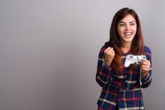 Young beautiful Indian woman wearing checked shirt against gray. Studio shot of young beautiful Indian woman wearing checked shirt against gray background Stock Photo