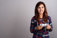 Young beautiful Indian woman wearing checked shirt against gray. Studio shot of young beautiful Indian woman wearing checked shirt against gray background Royalty Free Stock Image