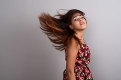 Young beautiful Indian woman wearing dress while flipping hair a. Studio shot of young beautiful Indian woman wearing dress while flipping hair against gray Royalty Free Stock Photography