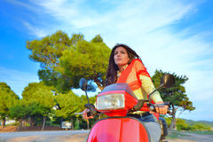 Young beautiful italian woman sitting on a italian scooter in Italy hills Royalty Free Stock Photo