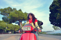 Young beautiful italian woman sitting on a italian scooter in Italy hills Royalty Free Stock Photography