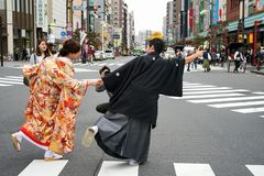 Young beautiful Japanese couple dressed in national Japanese costumes and photographed on street city Tokyo, Japan royalty free stock images