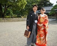 Young beautiful Japanese couple dressed in national Japanese costumes and photographed on street city Tokyo, Japan royalty free stock image