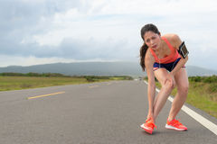 Young beautiful jogger running on road too tired. Leading ankle and knee pain uncomfortable, showing painful expression with mountain landscape Stock Photos