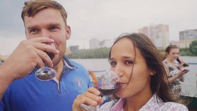 Young beautiful joyful couple rest on a yacht, drink wine in slow motion. 1920x1080 stock video footage
