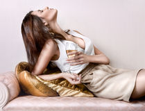Young beautiful lady. Closeup fashion portrait of young hot woman sitting relaxed on comfortable luxury sofa in vintage interior and drinking champagne or wine stock images