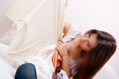 Young beautiful lady. Beautiful young slim woman on the bed indoors unpacking clothes from suitcase stock photo