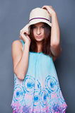 Young beautiful lady. Confident woman with arms near her head holding hat against a blue background royalty free stock images