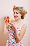 Young beautiful lady in curlers holding big red Royalty Free Stock Photography