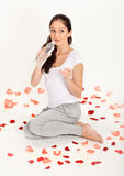 Young beautiful lady drinking gas water in bottle. Young beautiful lady drinking gas water sitting on the floor covered with rose petals Stock Images