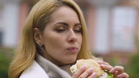 Young beautiful lady eating burger, harm of junk food, digestion problems risk. Stock footage stock video