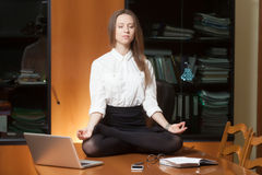 Young beautiful lady making yoga. Young beautiful lady in office sitting on the table in yoga pose Royalty Free Stock Images