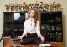 Young beautiful lady making yoga. Young beautiful lady in office sitting on the table in yoga pose and meditate with winner cups on background Royalty Free Stock Photo