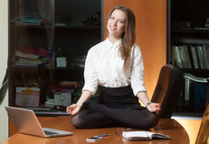 Young beautiful lady making yoga. Young beautiful lady in office sitting on the table in yoga pose and smiling Stock Image