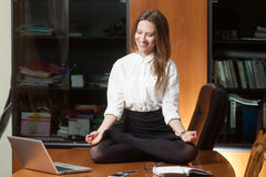 Young beautiful lady making yoga. Young beautiful lady in office sitting on the table in yoga pose and smiling Stock Photography